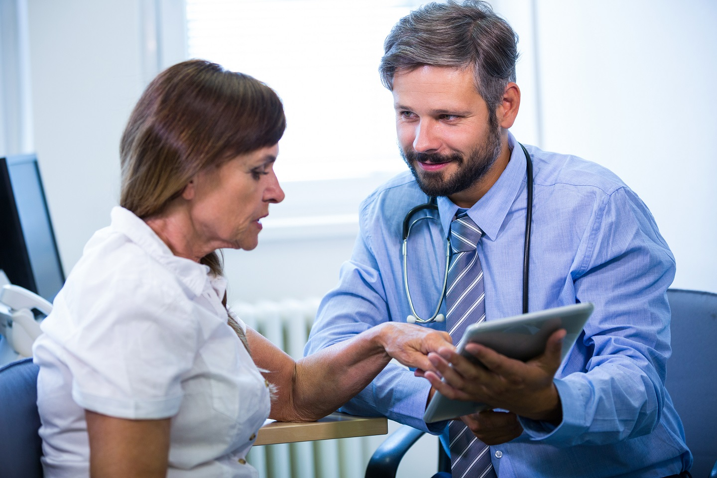 Male doctor discussing with patient over digital tablet at the hospital